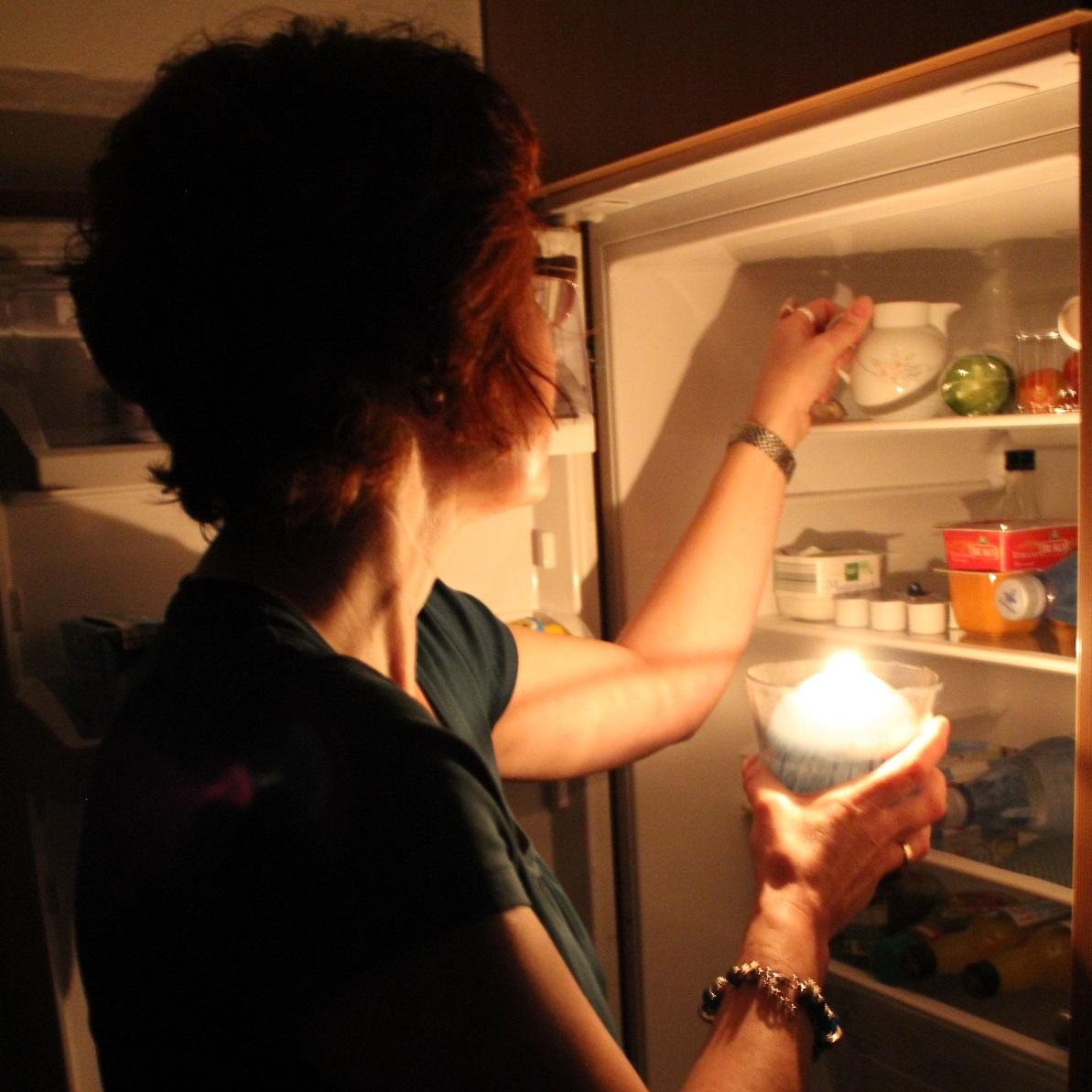 Eine Frau leuchtet während eines Stromausfalls mit einer Kerze in ihren Kühlschrank