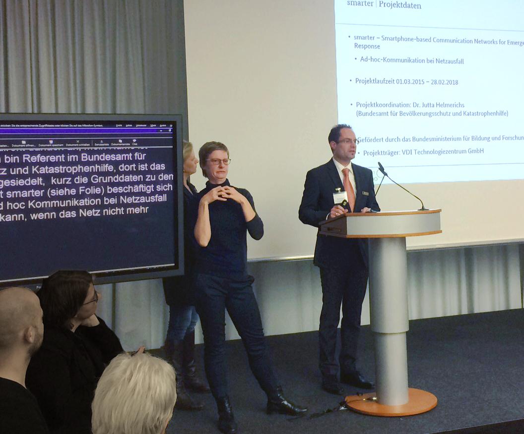 Thomas Knoch stellt das Projekt smarter vor und wird simultan in International Sign, in deutsche Gebärdensprache und in deutsche Schriftsprache gedolmetscht